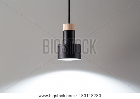 Luminous metal black lamp with light wooden part is hanging on the black cable on the gray background. Closeup photo. Horizontal.