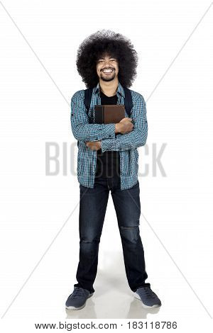 Afro college student looks confident while holds a book and stands in studio isolated on white background