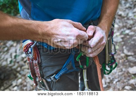 A man climber Untying the knot on a climbing harness. hands in chalk close up