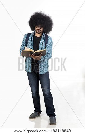 Afro male student reading his textbook while standing in studio isolated on white background
