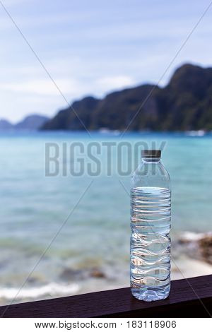 Bottle of drinking water on background of sea and mountains