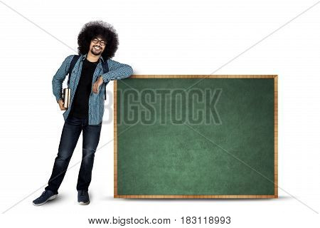 Afro student standing besides copy space on chalkboard while smiling at the camera isolated on white background