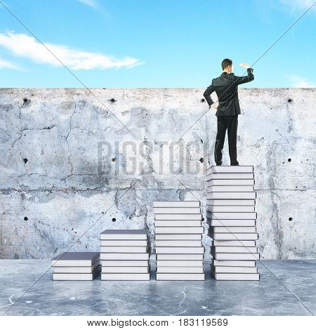 Young businessman on top of creative book ladder looking into the distance. Education concept. 3D Rendering