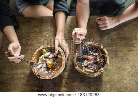 Female hands with forks and wooden bowls on the table. In the bowls there are exotic fruit mix. Shoot from above. Closeup. Horizontal.