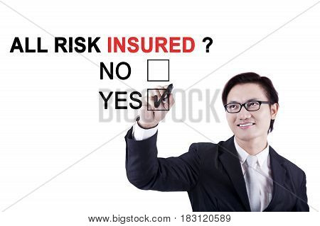 Asian male worker using a marker while approving about a question of all risk insured on the whiteboard