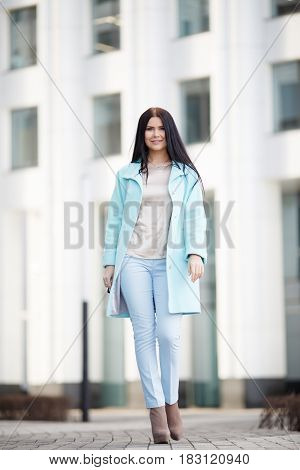 Beautiful brunette walking down street on building background
