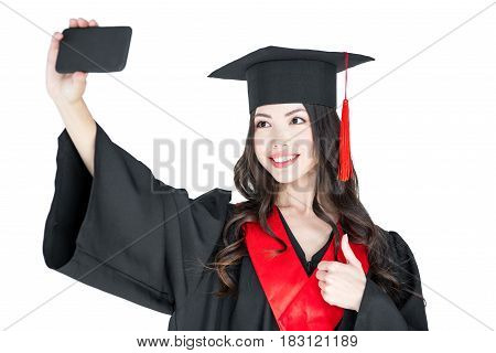 Smiling Young Brunette Woman In Mortarboard Taking Selfie On White