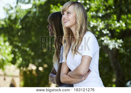 Joyous young blond woman looking away in town