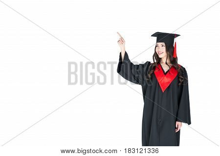 Beautiful Young Brunette Woman In Academic Gown Pointing Away With Finger