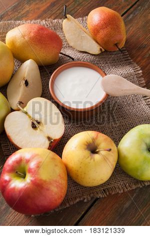 Homemade natural farmer yoghurt for breakfast in jar with fresh fruits - pears and apples on wooden desk, close-up, top view, vertical