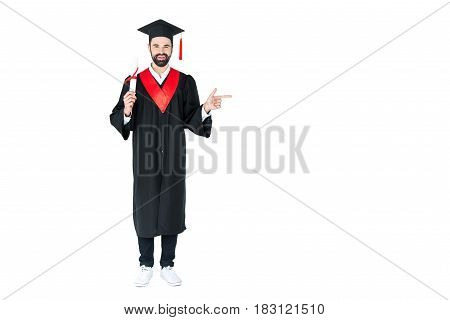 Full Length View Of Happy Young Student Holding Diploma And Pointing Away With Finger