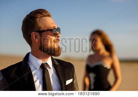 Beautiful Young Man With Smile In Suit Wear And Sunglasses Standing In Desert Enjoying Nature And Th