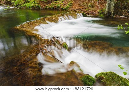 Mountain river  with mossy rocks. Long exposure of white water rapids and waves with rocks and moss. Grza river, Serbia