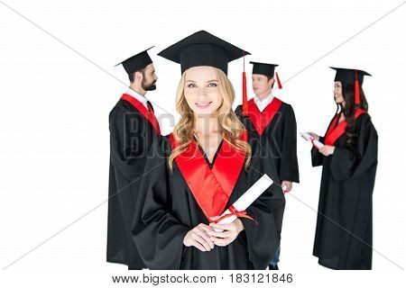 Happy Young Woman In Mortarboard Holding Diploma And Friends Standing Behind
