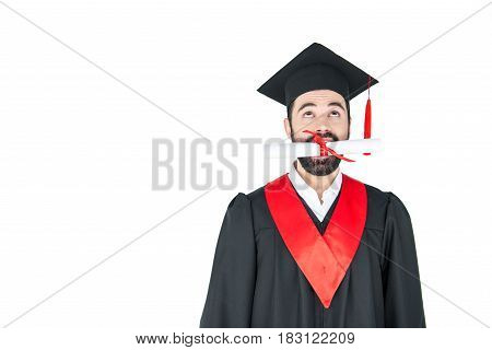 Happy Young Bearded Student Holding Diploma In Teeth On White