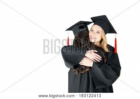 Two Young Happy Women In Mortarboards Hugging On White Background