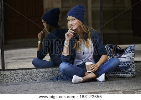 Young blond woman wearing headphones and hat in city smiling