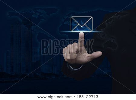Businessman pressing mail flat icon over world map and modern city tower Contact us concept Elements of this image furnished by NASA