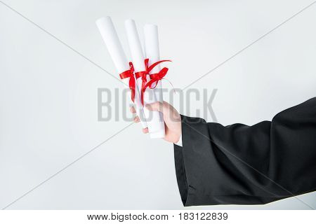 Close-up partial view of student holding diplomas on grey
