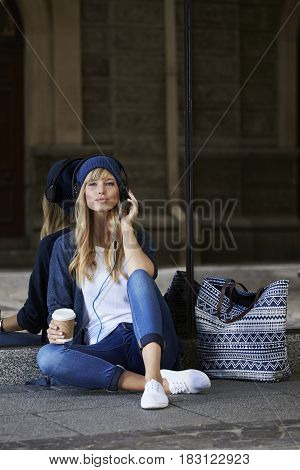 Beautiful woman relaxing with music in city portrait