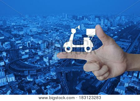 Motor bike icon on finger over modern city tower street and expressway Business delivery service concept