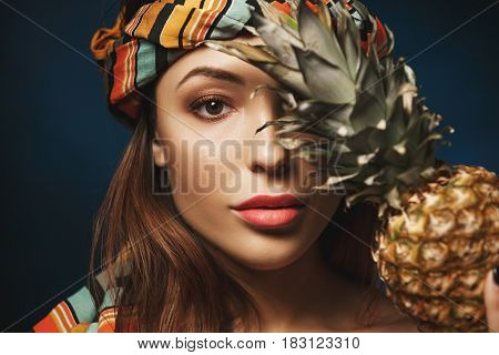 Closeup of young exotic woman in colourful bandana. Covering eye with pineapple. Isolated on blue.