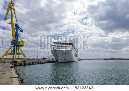 A high port crane in blue and yellow against the background of a dramatic sky and a large white ship