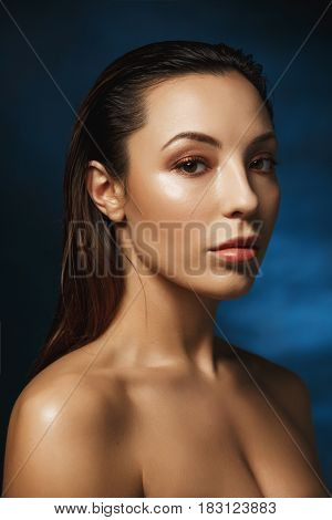Closeup portrait of naked woman with fashion make up, looking straight. Isolated on blue background.