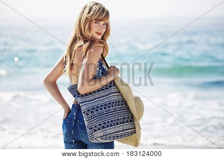 Beautiful blond beach babe with bag portrait