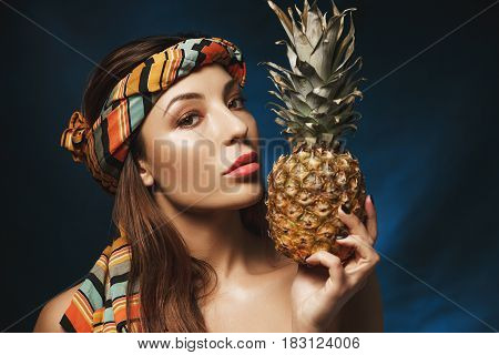 Gorgeous naked woman with colourful bandana on head, holding pineapple, looking straight at camera.