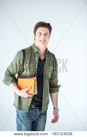 young student holding copybooks and book on white wth copy space