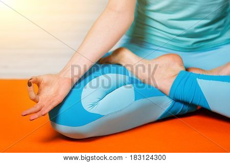 Young sports woman in lotus position on rug