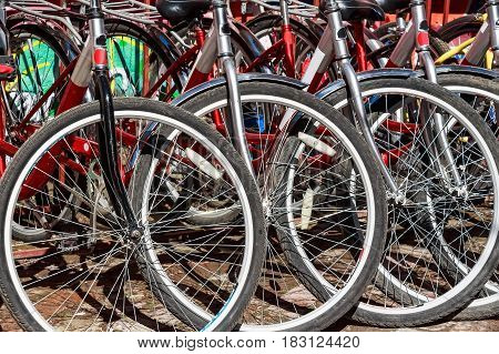 Closeup image of red bicycles parts with black tires