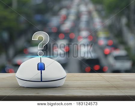 Question mark sign icon with wireless computer mouse on wooden table over blur of rush hour with cars and road Customer support concept