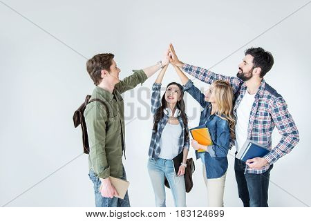 Four Young Students In Casual Clothes Holding Books And Giving Highfive On White