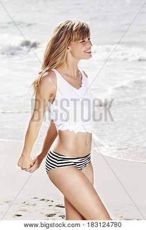 Bikini girl on beach smiling with ocean background