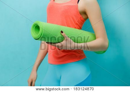 Young girl holds twisted fitness mat in gym