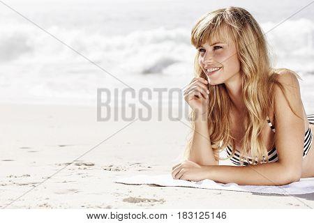 Beautiful blonde woman sunbathing on beach smiling