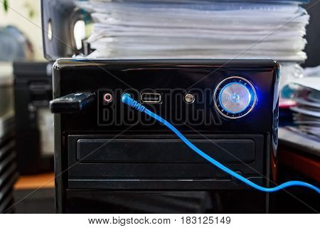 Close up of system unit of modern computer with flash stick in socket and blue headphones wire
