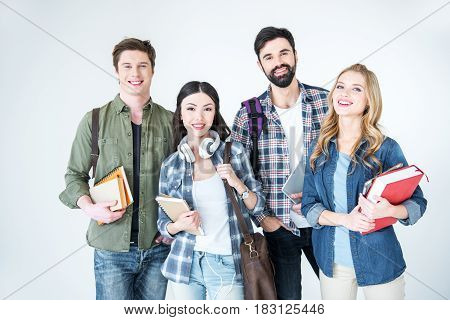 Four Young Students In Casual Clothes Holding Books On White