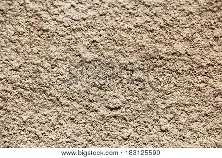 Grey wall with pattern of rough cracked cement plaster