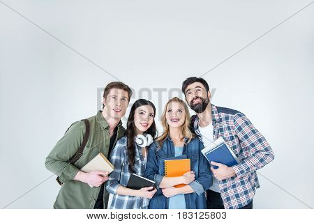 four young students in casual clothes holding book on white
