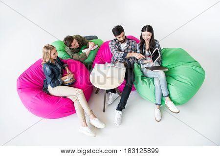 students sitting on beanbag chairs and studying with digital tablet in studio on white