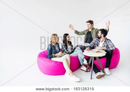 students sitting on beanbag chairs and studying in studio on white