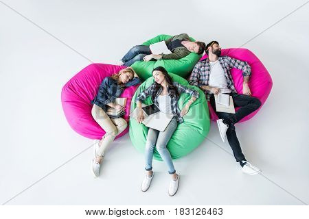 tired students sleeping in beanbag chairs with book in studio on white