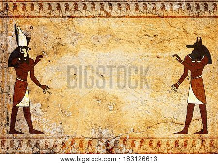 Grunge background with old stucco texture of yellow color and Egyptian gods Anubis and Horus images