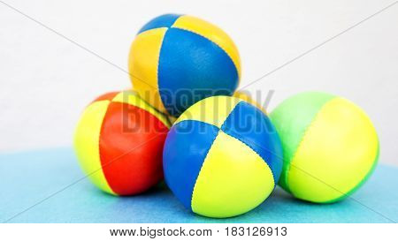 stack of colorful juggling balls on blue table with white background