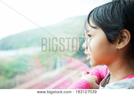 Cute little girl looking through the window inside a cable car at Ngong Ping 360 in Lantau Island Hong Kong