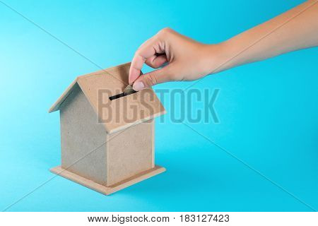 A female hand putting a coin into a money box. The concept of financial savings to buy house.
