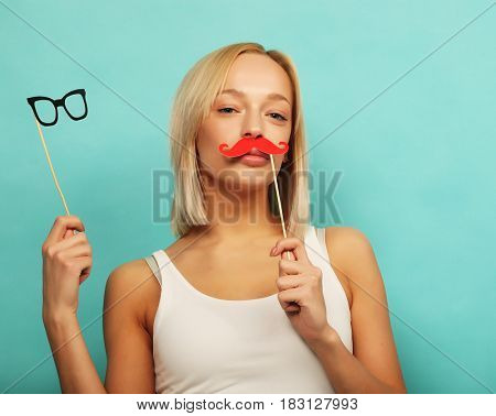 lifestyle and people concept: Happy girl wearing fake mustaches and glasses over yellow background.